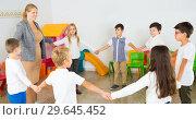 Купить «Children standing in circle holding hands with teacher», фото № 29645452, снято 17 января 2019 г. (c) Яков Филимонов / Фотобанк Лори
