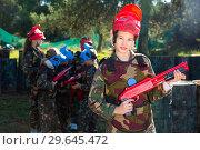 Купить «Teen girl wearing uniform and holding gun ready for playing with friends on paintball outdoor», фото № 29645472, снято 24 ноября 2018 г. (c) Яков Филимонов / Фотобанк Лори