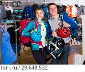 Купить «cheerful girl and guy select gear for hiking and camping in sports shop», фото № 29648532, снято 25 октября 2017 г. (c) Яков Филимонов / Фотобанк Лори