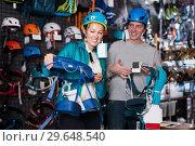 Купить «Portrait of happy couple looking climbing equipment», фото № 29648540, снято 25 октября 2017 г. (c) Яков Филимонов / Фотобанк Лори
