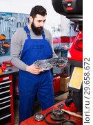 Купить «Male worker inspects parts for motorcycle», фото № 29658672, снято 16 января 2019 г. (c) Яков Филимонов / Фотобанк Лори