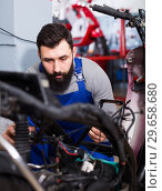 Купить «Worker repairing motorbike», фото № 29658680, снято 19 января 2019 г. (c) Яков Филимонов / Фотобанк Лори