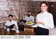 Купить «Young female waiter bringing order for visitors», фото № 29658704, снято 17 января 2017 г. (c) Яков Филимонов / Фотобанк Лори
