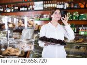 Купить «Seller offering tray of cakes», фото № 29658720, снято 24 января 2017 г. (c) Яков Филимонов / Фотобанк Лори