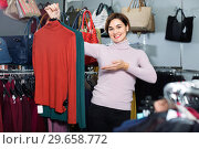 Купить «Female shopper examining turtleneck sweaters in women's cloths shop», фото № 29658772, снято 7 февраля 2017 г. (c) Яков Филимонов / Фотобанк Лори