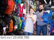 Купить «Couple choosing rucksack in store», фото № 29658780, снято 24 февраля 2017 г. (c) Яков Филимонов / Фотобанк Лори