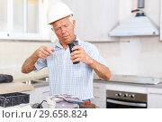 Купить «Man in hardhat engaged in renovation work», фото № 29658824, снято 19 июня 2018 г. (c) Яков Филимонов / Фотобанк Лори