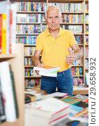 Купить «Intelligent older man holding out books to somebody while standing near racks», фото № 29658932, снято 11 июня 2018 г. (c) Яков Филимонов / Фотобанк Лори