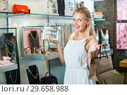 Купить «Portrait of young cheerful woman choosing earrings», фото № 29658988, снято 20 января 2019 г. (c) Яков Филимонов / Фотобанк Лори