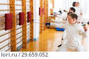 Купить «Group practicing fencing techniques in gym», фото № 29659052, снято 30 мая 2018 г. (c) Яков Филимонов / Фотобанк Лори