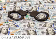 Купить «Steel black handcuffs lying on the background of american dollars», фото № 29659388, снято 4 января 2017 г. (c) FotograFF / Фотобанк Лори