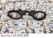 Купить «Steel black handcuffs lying on the background of american dollars», фото № 29659388, снято 4 января 2017 г. (c) FotograFF / Фотобанк Лори