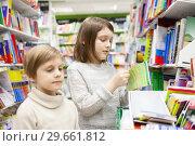 Купить «Two girls choosing books in bookstore for school», фото № 29661812, снято 21 ноября 2019 г. (c) Дарья Филимонова / Фотобанк Лори