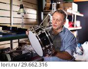 Купить «Adult man is choosing drum kit in music store.», фото № 29662316, снято 18 сентября 2017 г. (c) Яков Филимонов / Фотобанк Лори