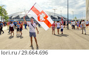 Купить «Russia, Samara, July 2018: an English football fan waving a national flag at the World Cup against the backdrop of the stadium.», фото № 29664696, снято 7 июля 2018 г. (c) Акиньшин Владимир / Фотобанк Лори