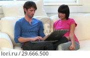 Купить «Young Couple on Sofa With Laptop», видеоролик № 29666500, снято 1 марта 2008 г. (c) Wavebreak Media / Фотобанк Лори