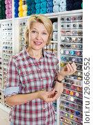 Купить «Female next to shelf with buttons», фото № 29666552, снято 23 мая 2019 г. (c) Яков Филимонов / Фотобанк Лори