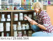 Купить «portrait of female customer standing next to different bands for sewing in shop», фото № 29666564, снято 18 июля 2019 г. (c) Яков Филимонов / Фотобанк Лори