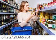 Купить «Positive female customer with basket holding canned goods in the food store», фото № 29666704, снято 11 апреля 2018 г. (c) Яков Филимонов / Фотобанк Лори