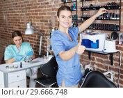 Купить «Smiling woman manicurist searching polish at shelves», фото № 29666748, снято 30 мая 2018 г. (c) Яков Филимонов / Фотобанк Лори