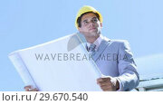 Купить «Architect holding plans checking the works», видеоролик № 29670540, снято 1 октября 2009 г. (c) Wavebreak Media / Фотобанк Лори