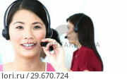 Купить «Close up of Asian woman working in a call center», видеоролик № 29670724, снято 3 октября 2009 г. (c) Wavebreak Media / Фотобанк Лори