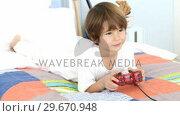 Купить «Little boy playing video games on bed», видеоролик № 29670948, снято 10 октября 2009 г. (c) Wavebreak Media / Фотобанк Лори