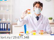 Купить «Young handsome chemist working in the lab», фото № 29671348, снято 6 августа 2018 г. (c) Elnur / Фотобанк Лори