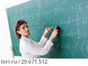 Купить «Female math teacher in front of the chalkboard», фото № 29671512, снято 31 октября 2018 г. (c) Elnur / Фотобанк Лори