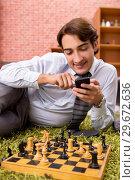 Купить «Young handsome boss playing chess during break», фото № 29672636, снято 10 сентября 2018 г. (c) Elnur / Фотобанк Лори