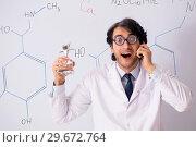 Купить «Young funny chemist in front of white board», фото № 29672764, снято 9 октября 2018 г. (c) Elnur / Фотобанк Лори