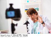 Купить «Chemist blogger recording video for his blog», фото № 29675164, снято 25 сентября 2018 г. (c) Elnur / Фотобанк Лори
