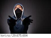 Купить «Young gangster in hood on grey background», фото № 29675604, снято 27 сентября 2018 г. (c) Elnur / Фотобанк Лори