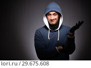 Купить «Young gangster in hood on grey background», фото № 29675608, снято 27 сентября 2018 г. (c) Elnur / Фотобанк Лори
