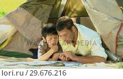 Купить «Father and son looking at a map near a tent», видеоролик № 29676216, снято 10 ноября 2010 г. (c) Wavebreak Media / Фотобанк Лори