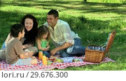Купить «Parents feasting at a picnic with children on a tablecloth», видеоролик № 29676300, снято 10 ноября 2010 г. (c) Wavebreak Media / Фотобанк Лори