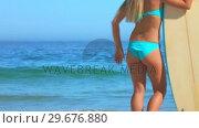Купить «Woman looking at the sea before going surfing», видеоролик № 29676880, снято 15 ноября 2010 г. (c) Wavebreak Media / Фотобанк Лори