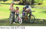 Купить «Young couple with their two children ready to go cycling», видеоролик № 29677124, снято 16 ноября 2010 г. (c) Wavebreak Media / Фотобанк Лори