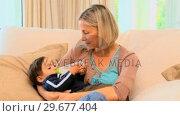 Купить «Young mother bottlefeeding baby on sofa», видеоролик № 29677404, снято 6 ноября 2010 г. (c) Wavebreak Media / Фотобанк Лори