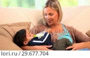 Купить «Mother bottlefeeding her baby on sofa», видеоролик № 29677704, снято 6 ноября 2010 г. (c) Wavebreak Media / Фотобанк Лори