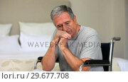 Купить «Pensive man in a wheelchair », видеоролик № 29677708, снято 6 ноября 2010 г. (c) Wavebreak Media / Фотобанк Лори