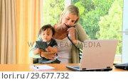 Купить «Woman carrying baby and working on laptop », видеоролик № 29677732, снято 6 ноября 2010 г. (c) Wavebreak Media / Фотобанк Лори