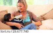 Купить «Relaxed mother bottlefeeding her child », видеоролик № 29677740, снято 6 ноября 2010 г. (c) Wavebreak Media / Фотобанк Лори