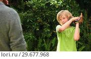 Купить «Boy playing with baseball with father in garden», видеоролик № 29677968, снято 6 ноября 2010 г. (c) Wavebreak Media / Фотобанк Лори