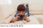 Купить «Boy playing video games», видеоролик № 29678872, снято 3 ноября 2011 г. (c) Wavebreak Media / Фотобанк Лори