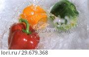 Купить «Peppers falling into water in super slow motion», видеоролик № 29679368, снято 26 января 2012 г. (c) Wavebreak Media / Фотобанк Лори