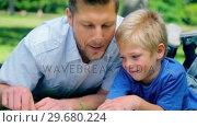Купить «Father talking to his son and pointing to the ground as they lie in the grass», видеоролик № 29680224, снято 17 ноября 2011 г. (c) Wavebreak Media / Фотобанк Лори