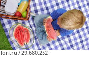 Купить «Overhead shot of a boy sitting on a picnic blanket while eating a slice of watermelon and smiling», видеоролик № 29680252, снято 17 ноября 2011 г. (c) Wavebreak Media / Фотобанк Лори
