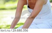 A woman stretches outward as she holds a yoga position. Стоковое видео, агентство Wavebreak Media / Фотобанк Лори