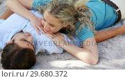Купить «A woman lying on her boyfriend talk as they smile», видеоролик № 29680372, снято 17 ноября 2011 г. (c) Wavebreak Media / Фотобанк Лори